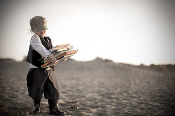 Little boy in victorian era clothing carrying books along beach
