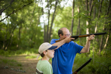 Man and young boy aiming rifles in forest
