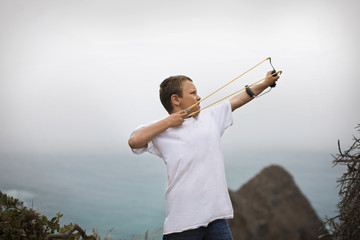 Boy shooting slingshot from high up