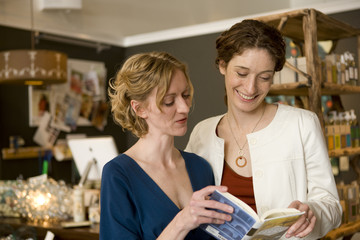 Women looking at book in store