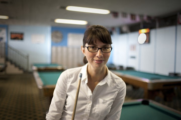 Portrait of a young woman holding a pool cue in a pool hall.