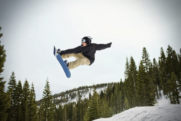 Young man jumping mid-air while riding his snowboard  outdoors in the snow.