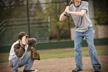 Teenage boy crouching with a baseball mitt behind a batsman on a sports field.
