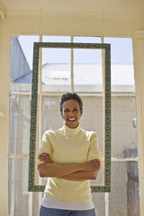 Portrait of a laughing mid-adult woman standing in front of a window with her arms crossed.