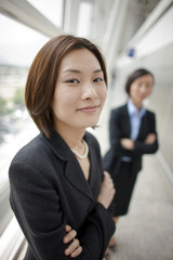 Portrait of Chinese businesswoman with her colleague in the background.