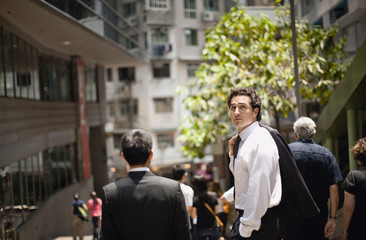 Businessman looking over his shoulder in a crowded street.