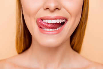 Closeup cropped half face shot of femenine gorgeous playful charming adorable nude natural lady with white healthy teeth gesturing showing tongue out isolated on beige background, correction concept
