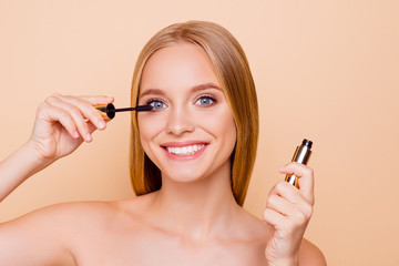 Portrait of pretty, charming, cheerful, positive, toothy girl with beaming smile applying black mascara looking at camera looking at camera isolated on beige background
