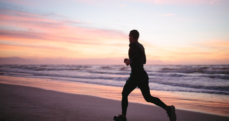 Healthy man jogging along the sea shore
