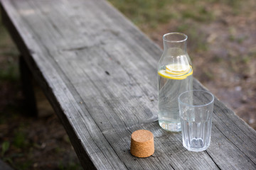 A bottle of water with lemon and a glass. A bench on which a refreshing drink is placed.