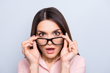 Portrait of impressed, shocked, angry, stressed woman holding eyelets of glasses on her face with two hands looking out spectacles with wide open mouth isolated on grey background