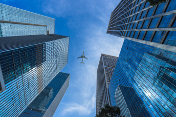 Tall city buildings and a plane flying overhead.