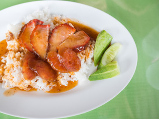 Red pork with rice, topped with red water in the dish, white on green table.