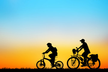 Silhouette love couple  and bike relaxing on sunset