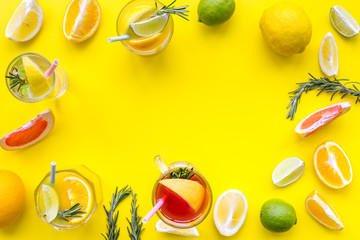 Concept of alcoholic cocktail with fruits. Glass with beverage near oranges, grapefruit, lime and rosemary on yellow background top view copy space