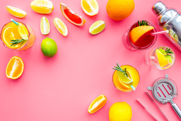 Bartender workplace for make fruit cocktail with alcohol. Shaker, strainer and other bar tools near citrus fruits and glass with cocktail on pink background top view copy space