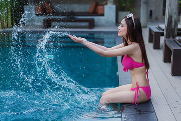 woman sitting on edge of pool and playing water splash