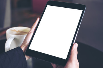 Top view mockup image of hands holding black tablet pc with white blank screen and coffee cup on table background