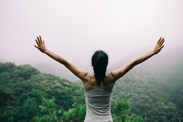 Happy woman with outstretched arms enjoying the view on morning mountain valley