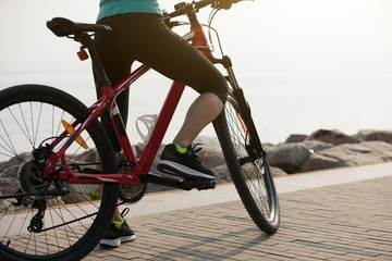 Woman cyclist riding mountain bike on seaside