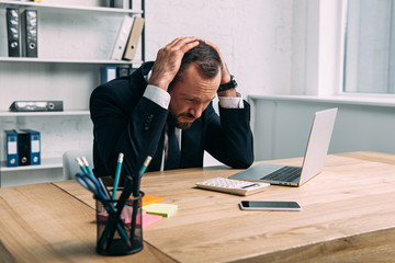 portrait of stressed businessman at workplace with laptop in office