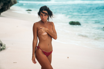 Portrait of a gorgeous girl without a bra on the beach. A model dressed in red swimsuit posing on the beach and covering her breast with her hand.