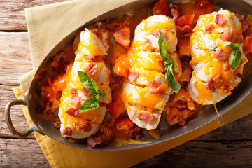 Spicy chicken fillet baked with bacon, tomatoes and cheddar cheese close-up in a pan. horizontal top view
