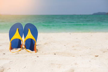 Beach sandals on the sandy sea coast, summer concept holiday and vacation concept. Tropical sea