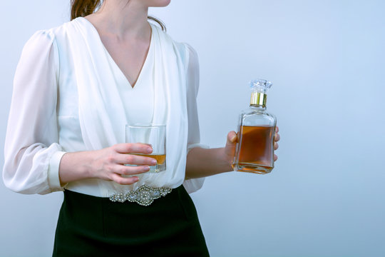 young woman in a dress with a glass in one hand and a bottle of whiskey in the other hand. female alcoholism.