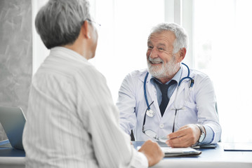Senior male Doctor and Asian male patient are talking.