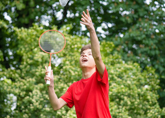 Young teen boy playing badminton in meadow with forest in background. Child with badminton rackets in hand. Kid have fun in summer park at day.