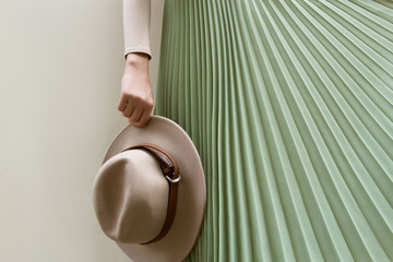 Hat, beige blouse and turqoise pleats skirt on light street backgraund.  Fashion and stylish concept. Wall mural