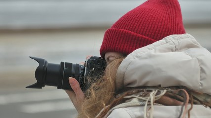 Young beautiful woman in red hat wearing sporty warm clothes and rollers, sitting on the asphalt road and taking pictures on a vintage camera