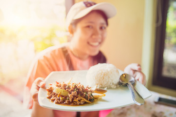 Thailand Street food delicious tasty of jasmine rice top with pork chop stir-fried with basil leaf and fried egg most popular food present to tourist by Thai cute women