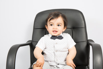 young boy sitting on business chair presents himself as a businessman