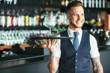 Smiling waiter ready to serve a cocktail