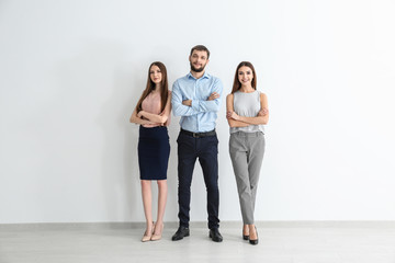 Young people standing together on white wall background. Unity concept