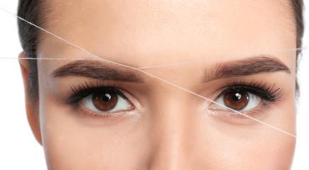 Young woman correcting eyebrow shape with thread, closeup