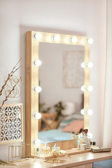 Mirror with light bulbs and cosmetic products on dressing table indoors