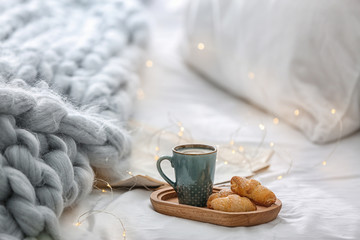 Cup of coffee and croissants on bed at home
