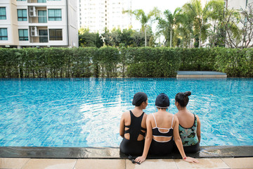 three women friends having fun together in swimming pool together having fun enjoying summer at vacation resort smiling in women holiday concept