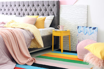 Stylish room interior with comfortable bed and rainbow carpet