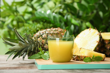 Composition with delicious pineapple juice on table against blurred background