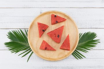 Watermelon on wooden plate decorate with fern leaves on white wood background