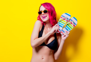 Young pink hair girl in bikini and orange glasses with flip flops. Portrait isolated on yellow background