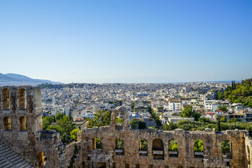 View of Athens cityscape through ancient stone theatre seeing lowrise white buildings architecture, mountain, trees and clear blue sky background