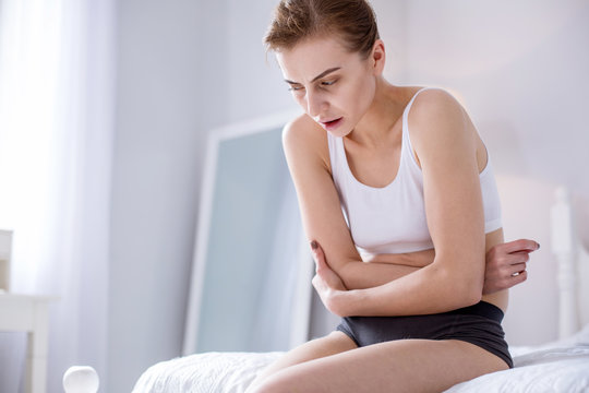 From hunger. Depressed sad woman holding her stomach while feeling pain