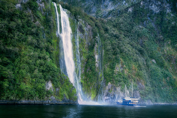 A Cruise boat in front of Stirling Falls at Milford Sound, New Zealand, South Island.