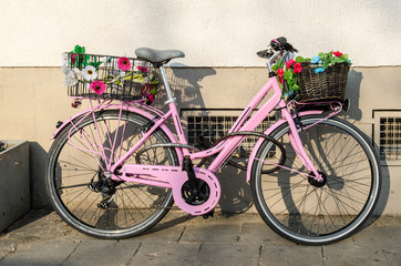 old pink bicycle with flowers in front of a building