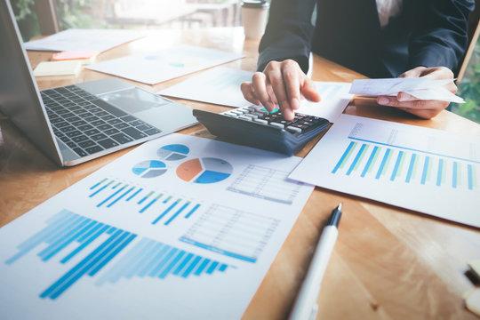 Female accountant or banker use calculator.